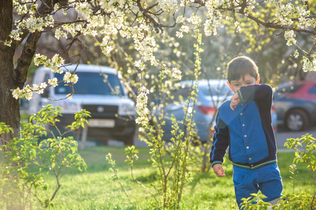 Allergy. Little boy is blowing her nose near spring tree in bloom. Closeup portrait. Stock Photo