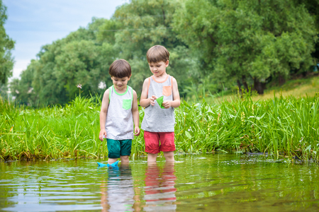 Two little sibling brothers playing with paper boats in a river or lake on warm and sunny summer day. Active leisure for children. Kid boy best friends having fun together outdoors.