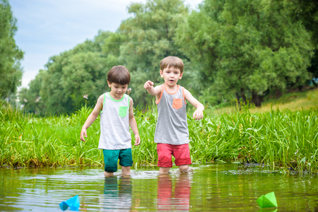 Two brothers playing with paper boats in a river or lake on warm and sunny summer day.