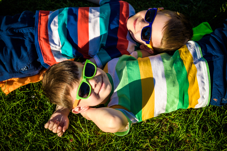 Happy cheerful smiling children, laying on a grass, wearing sunglasses, smiling at the camera, shot from above. Happy childhood friendship concept. 스톡 콘텐츠