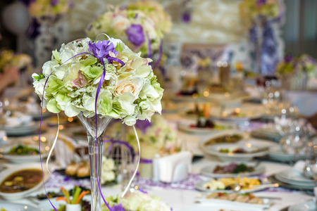 Table setting at a luxury wedding reception. Example of festive decorating. Real flowers on table for bride and groom.