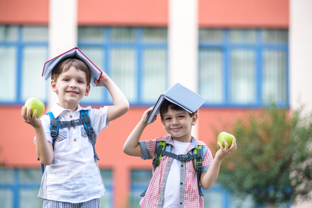 Child going to school. two boy friend holding books on head house roof, first school day. Little students excited to be back to school. Beginning of class vacation. Kids eating apple in yard
