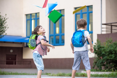 Happy children - two boys friends with books and backpacks on the first or last school day. Schoolchildren celebrating end of term. Students to complete academic year. Full length outdoor portrait.
