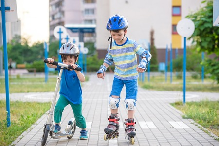 Two kid boy on roller skates and his sibling brother on scooter wrapped in park. Children wearing protection pads for safe roller skating ride. Active outdoor sport for kids. Stock Photo