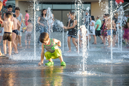 KYIV, UKRAINE AUGUST 13, 2017: Happy kids have fun playing in city water fountain on hot summer day. Parents with their children. Active family leisure, ecology concept. Editorial