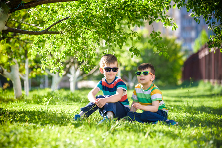 Happy summer holidays. Two children on a green lawn at a summer park. Sibling brother boys sitting in park wearing sunglasses on blooming trees background. Kids happy and smiling friendship concept.