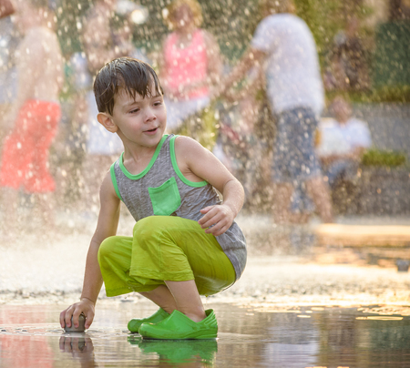 Excited boy having fun between water jets, in fountain. Summer in the city. Kid happy smile face hold jet with hand. Ecology concept. Stockfoto