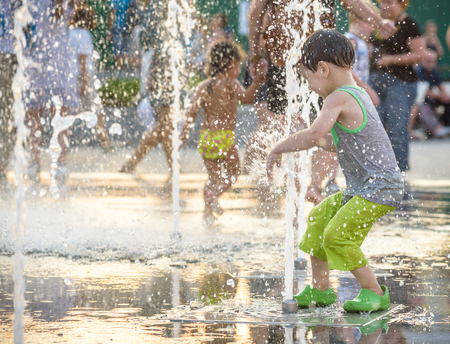 Excited boy having fun between water jets, in fountain. Summer in the city. Kid happy smile face. Ecology concept.