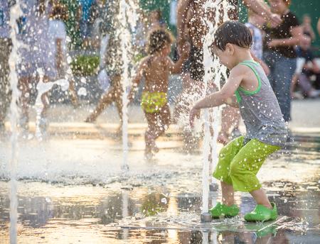 Opgewonden jongen met plezier tussen waterstralen, in fontein. Zomer in de stad. Kind blij lachgezicht. Ecologie concept.