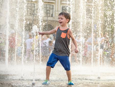 Aufgeregter Junge, der Spaß zwischen Wasserstrahlen im Brunnen hat. Sommer in der Stadt. Kind schlug Wasser mit Hand glückliches Lächelngesicht. Ökologiekonzept.