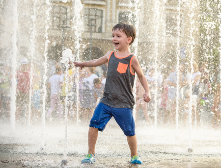 Excited boy having fun between water jets, in fountain. Summer in the city. Kid hit water with hand happy smile face. Ecology concept. Zdjęcie Seryjne