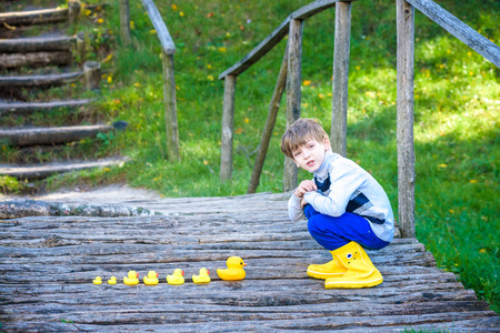 Adorable child, boy, kid, playing in park with rubber ducks on ancient wooden rustic bridge, having fun. Childhood happiness relax adventure friendship concept. Sunny autumn day at forest park.