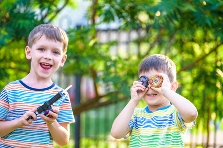 Two Boys playing with modern spin top outdoors. Entertainment game for children. Top, triggered by a trigger. Kids having a tournament on arena or battle field. Reklamní fotografie