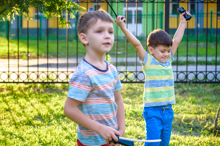 Two Boys playing with modern spin top outdoors. Entertainment game for children. Top, triggered by a trigger. Kids having a tournament on arena or battle field. Archivio Fotografico