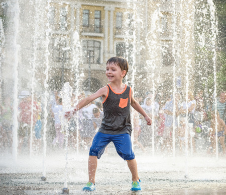 Excited boy having fun between water jets, in fountain. Summer in the city. Kid hit water with hand happy smile face. Ecology concept. Stockfoto