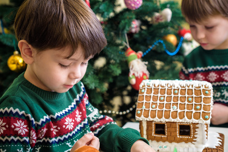 Two sweet boys, brothers, making gingerbread cookies house, decorating at home in front of the Christmas tree, child playing and enjoying, Christmas concept.