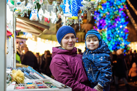 Happy family spend time at a Christmas street market fair in the old town. Holidays, Christmas, Family concept. Mother and son at winter outdoor among Christmas decorations Reklamní fotografie
