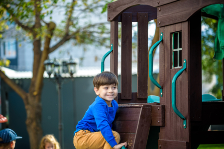 Little boy climbing ladder on slide at playground. Child is 5 7 year age. Caucasian, casual dressed in jeans and pullover. Children playing outdoors in summer. Healthy childhood concept.