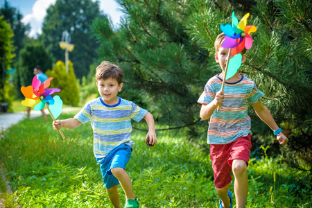 Two happy children playing in garden with windmill pinwheel. Adorable sibling brothers are best friends. Cute kid boy smile spring or summer park. Outdoors leisure friendship family concept.