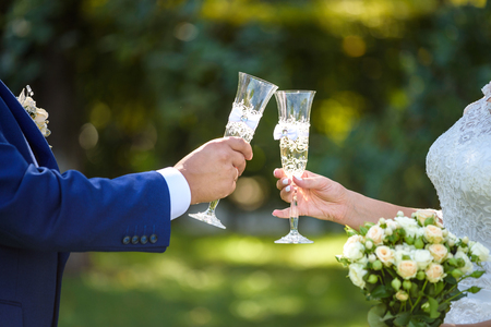 Bride and groom at the wedding table. holding a glass of champagne.