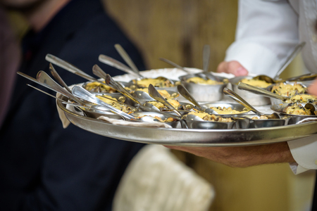 Waiter carrying plates with meat dish on some festive event, party or wedding reception. Stock Photo