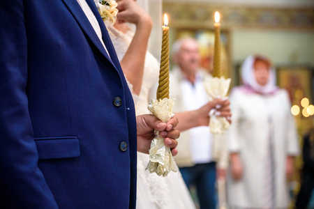 Bride and groom stand with crowns during the ceremony in church.