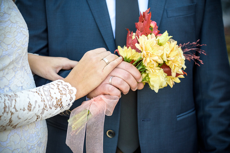 Close-up. Hand of bride and groom. Bride and groom hold hands. Focus on the rings. Bouquet in hand. 스톡 콘텐츠