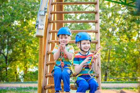 Twin brothers climbing in adventure park is a place which can contain a wide variety of elements, such as rope climbing exercises, obstacle courses and zip-lines. Kids boys sitting on wooden stairs.
