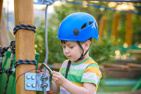 Little cute boy enjoying activity in a climbing adventure park on a summer sunny day. toddler climbing in a rope playground structure. Safe Climbing extreme sport with helmet and Carabiner. insurance Reklamní fotografie