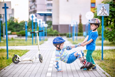 Dos niños hermanos hermanos juntos en el parque, ayuda al niño con patines a ponerse de pie después de la caída. Tiempo de vacaciones de verano de amistad y ocio activo con concepto de familia. Foto de archivo