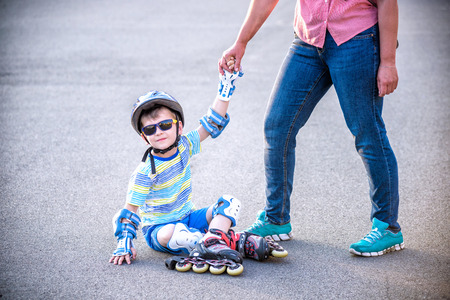 Preschooler falls over while rollerblading with mother in the park. Little boy learning to roller skate. Children wearing protection pads for safe ride. Active outdoor sport for kids.