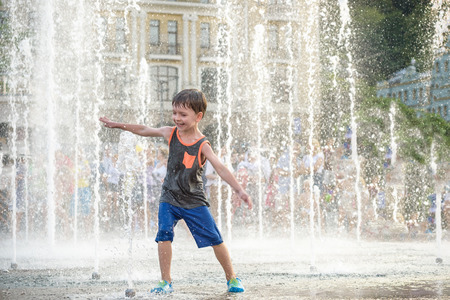Excited boy having fun between water jets, in fountain. Summer in the city. Kid hit water with hand happy smile face. Ecology concept. Standard-Bild