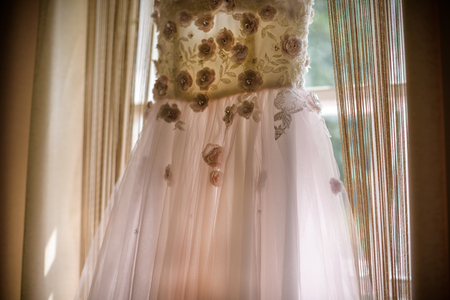 Elegant pink rose wedding dress with a train hanging on window. Wedding morning.