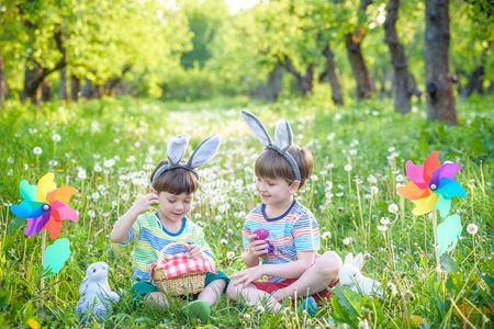 children having fun and playing with easter eggs. two cheerful boys sit on the lawn after Easter eggs hunt.