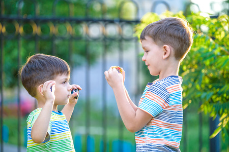 Two brother boy playing with modern spin top outdoors. Entertainment game for children. Top, triggered by a trigger. Kids demonstrate two different variants choosing which is better.