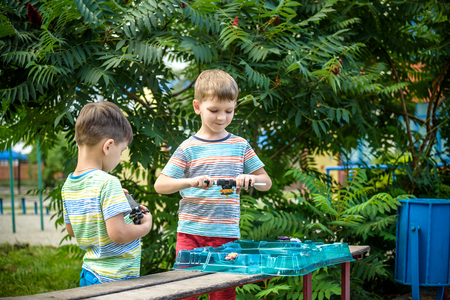 Two Boys playing with modern spin top outdoors. Entertainment game for children. Top, triggered by a trigger. Kids having a tournament on arena or battle field. Фото со стока