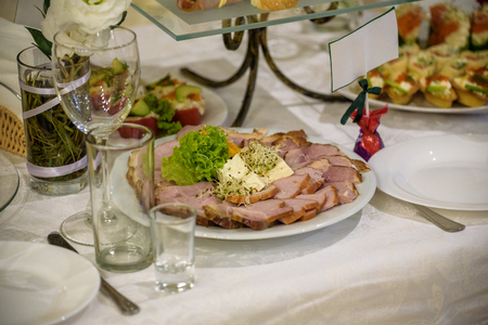 catering table set service with silverware and glass stemware at restaurant before party.