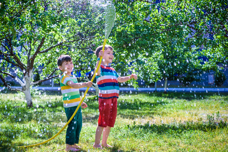 Brothers having fun splash each other with water in the village. Boys having fun with watering fruit garden in village outdoors. Funny holiday leisure water for children.