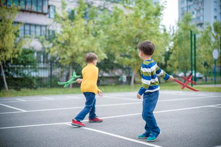 Heureux deux frères enfants jouant avec un avion jouet sur fond de ciel bleu d'été. Les garçons jettent un avion en mousse en ville. Meilleur concept d'enfance.