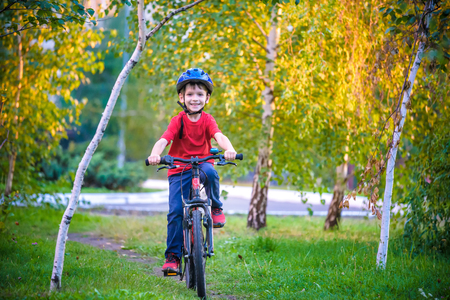 Happy kid boy of 6 years having fun in autumn forest with a bicycle on beautiful fall day. Active child making sports. Safety, sports, leisure with kids concept. Imagens