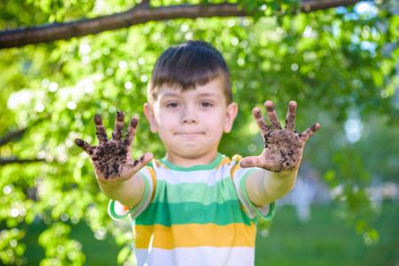 Ein junger kaukasischer Junge, der seine schmutzigen Hände nach dem Spielen in Schmutz und Sand im Freien sonnigen Frühlings- oder Sommerabend auf Blütenbaumhintergrund zeigt. glückliches Kindheitsfreundschaftskonzept. Standard-Bild