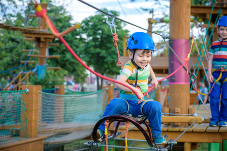 Little cute boy enjoying activity in a climbing adventure park on a summer sunny day. toddler climbing in a rope playground structure. Safe Climbing extreme sport with helmet and Carabiner. insurance Standard-Bild - 122384063