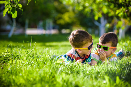 Happy smiling boy sibling brother relaxing on the grass. Close up view with copy space. Preschool kids wearing sunglasses summer holiday camp. Relaxation happy childhood friendship concept.