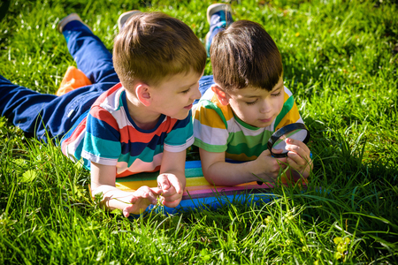 Beautiful happy children, boy brothers, exploring nature with magnifying glass, summertime. Preschool kids rest in summer holiday camp. Relaxation happy childhood friendship concept.
