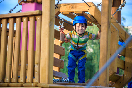 Little cute boy enjoying activity in a climbing adventure park on a summer sunny day. toddler climbing in a rope playground structure. Safe Climbing extreme sport with helmet and Carabiner. insurance Banco de Imagens
