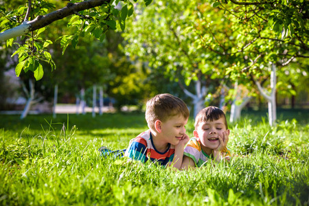 Happy children having fun outdoors. Kids playing in summer park. Little boy and his brother laying on green fresh grass holiday camp. Relaxation happy childhood friendship concept.