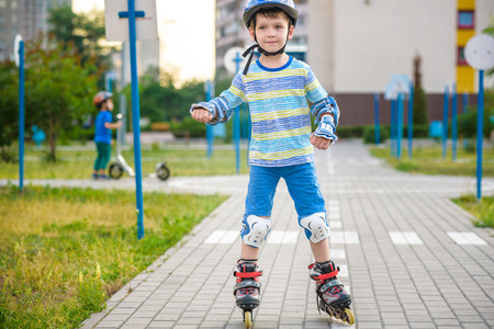 Two kid boy on roller skates and his sibling brother on scooter wrapped in park. Children wearing protection pads for safe roller skating ride. Active outdoor sport for kids.