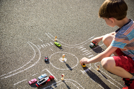 Funny kid boy having fun with picture drawing traffic car with chalks. Creative leisure for children outdoors in summer. Difficult traffic rules concept.