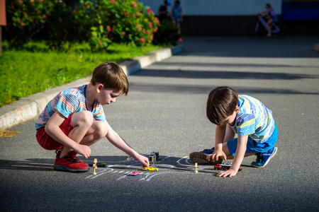 Two brothers sibling kid boy having fun with picture drawing traffic car with chalks. Creative leisure for children outdoors in summer. Difficult traffic rules education friendship concept. Banco de Imagens