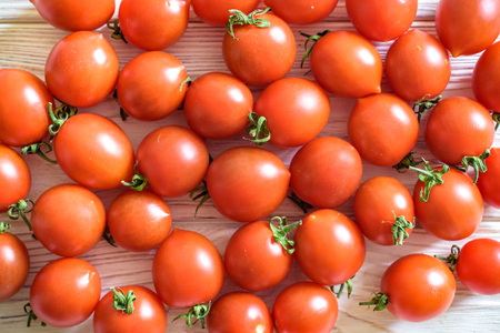 Cherry tomatoes. Tomatoes on a branch. Background of tomatoes. Vegetables and fruits. Healthy eating. Stock Photo